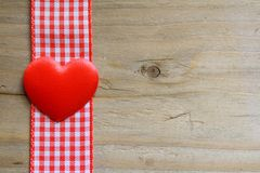 Heart and gingham. A red love heart on gingham ribbon on a rustic wooden surface Stock Photos