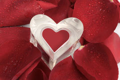 Heart of glass and rose petals. Heart peaking through rose petals with water droplets Stock Photography