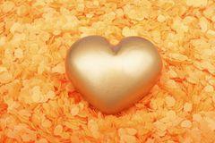Heart from gold in confetti Royalty Free Stock Image