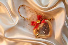 Heart on golden silk for St Valentine's day Royalty Free Stock Images