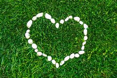 Heart on the grass lined with stones. Valentine`s day. Romantic concept. Background stock images