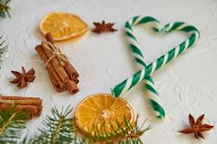 Heart of green candy cones and blurred Christmas tree branch with christmas spices - cinnamon sticks, anise stars, dried oranges Stock Photos