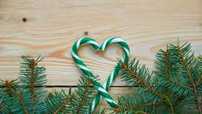 Heart of green candy cones and Christmas tree branches on the brown wooden background with free copy space.  New year or Valentine. S day food decorations with Stock Images
