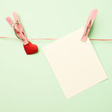 Heart and greeting card attached with a clothespin Royalty Free Stock Photo