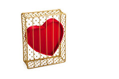 Heart In Guilded Cage. A red heart shape in a closed gold guilded cage, which could represent things like hiding feelings, feeling unloved, alone, emotionless Royalty Free Stock Image