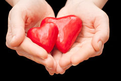 Heart in hand. Plasticine heart in hand on a black background Stock Image