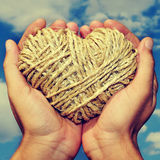 Heart in the hand. Someone holding a heart-shaped coil of rope in his hands in the sky Stock Photo