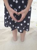 Heart hand. Girl making a heart with her hands, feet in the sand Stock Photos