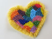 Heart (hand-made, beadwork). Colorful hand-made heart, decorated with different seed beads and yellow fringe Stock Images