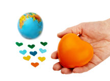 Heart  in hand over the globe and small hearts Stock Photos
