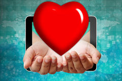 Heart on hand pushing out of tablet Stock Photo