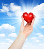 Heart in hand. On sunny sky Royalty Free Stock Images