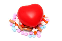Heart and handful of drugs Stock Photos