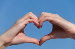 Heart from hands. Heart shaped from hands against clear blue sky Royalty Free Stock Photos