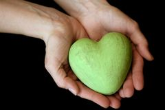 Heart and hands. Green ceramic hands holding in two hands on black background royalty free stock photography