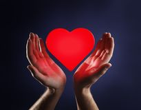 Heart and hands. Hands of a man and a red glowing heart stock photo