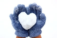 Heart in hands. Heart made from snow in females palms (hands)  with blue gloves isolated on white Royalty Free Stock Photo