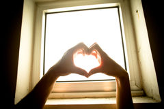 Heart of Hands. A man and woman's hand making a heart shape in front of a brightly lit window Stock Photo