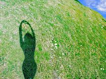 Heart Hands. A woman's shadow makes a heart shape against a green hillside. Can denote cardiac health, caring for the environment, etc Royalty Free Stock Photography