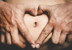 Heart from hands on a big belly Stock Photography