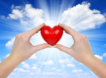 Heart in hands. On blue sky Royalty Free Stock Photo