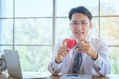 Heart in the hands of the doctor with stethoscope who mediates h. Ealth. Love concept. Health concept. selective focus Stock Image