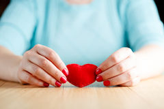 Heart in hands, female holds handmade sewn soft toy Royalty Free Stock Image