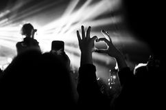 Heart of the hands. Fingers. Heart hands. The gesture of love. Concert in the heart of the glare of floodlights. Black and white stock photos