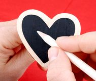 Heart in hands inscribed with white chalk on red background Stock Photos