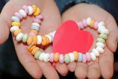 Heart in hands. Little child holding paper heart in hands and sweet necklace royalty free stock image