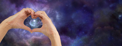 Heart hands loving the Universe. Female hands making a heart shape on a wide deep space background showing a nebula behind the heart shape royalty free stock image