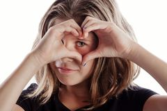 Heart hands around eye meaning I love you - inspiration for meme or poster. Young girl with black shirt isolated on white background in love poses - love heart stock photo