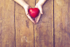 Heart in hands. Red heart in hands over vintage wooden background royalty free stock photography