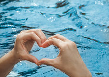Heart from hands on swimming pool