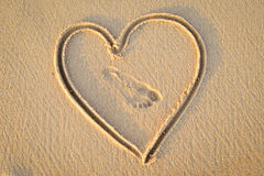 Heart handwrited on golden sand with foot print in Stock Photos