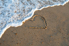 Heart handwritten on a sand of beach with wave Stock Photo