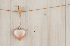 Heart hanging on the clothesline. On old wood background Stock Images