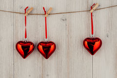 Heart hanging on the clothesline. On old wood background Stock Photo