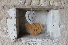 A heart hanging in a hole in a stone wall Royalty Free Stock Photography