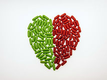 Heart that heals. As a dietary supplement tablets arranged in a heart shape divided into red and green royalty free stock photography