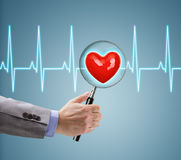 Heart health checkup. Doctor with magnifying glass on a heart and ecg diagram Stock Images
