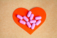 Heart health concept. Pink Pills on Red Heart Stock Image