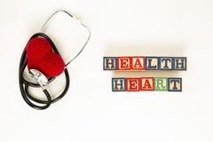Heart health and prevention concept. Stethoscope and red heart of crochet on white isolated background with space for text.  stock image