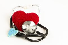Heart health and prevention concept. Stethoscope and red heart of crochet on white isolated background with space for text.  royalty free stock photo