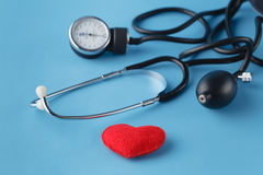 Heart healthcare concept, thonometer and toy heart on blue backg Royalty Free Stock Photos