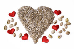 Heart Healthy. A healthy heart made from sunflower seeds (Shelled) with Pistachios and red hearts Royalty Free Stock Photography
