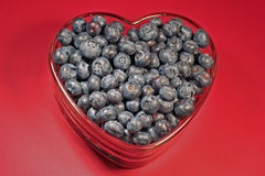 Heart-healthy blueberries. Fresh, heart-healthy blueberries in a heart-shaped glass dish isolated on a red background Stock Image