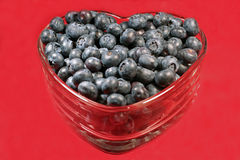 Heart-healthy blueberries. Fresh, heart-healthy blueberries in a heart-shaped glass dish isolated on a red background Royalty Free Stock Photo