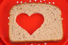 Heart Healthy Bread. Slice of whole wheat bread with heart shape cut out of center Stock Photos