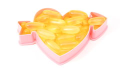 Heart Healthy Fish Oil. Fish oil pills inside of a heart showing the heart healthiness Royalty Free Stock Photos